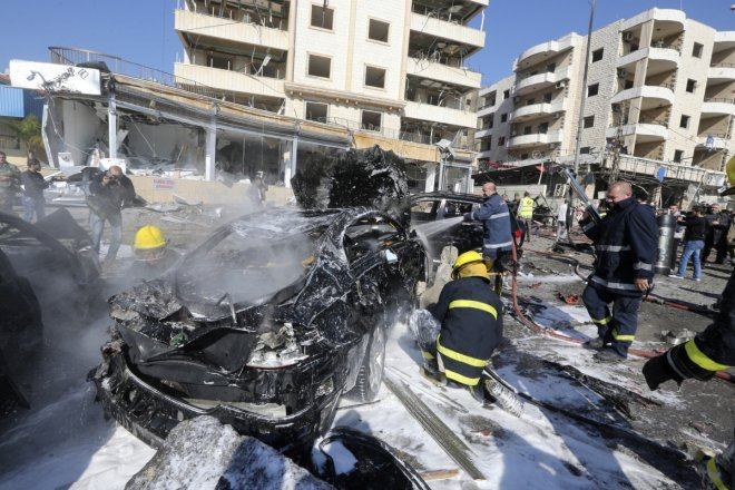 Civil defence members put out a fire at the site of an explosion in the southern suburbs of Beirut