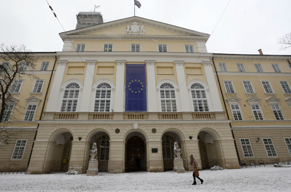 A woman walks past a building with a European Union flag in the western Ukranian city of Lviv