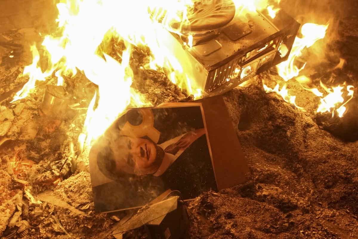 A portrait of Ukrainian President Viktor Yanukovich burns near the destroyed building of the security service in Lviv