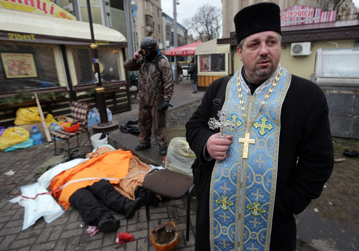 An Orthodox priest holds a cross as dead bodies are seen on the ground following violence in Independence Square in Kiev