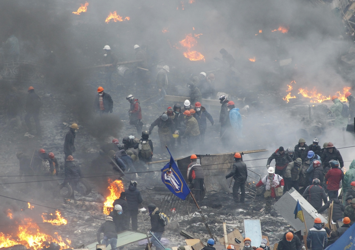 Anti-government protesters carry an injured man on a stretcher in Independence Square in Kiev