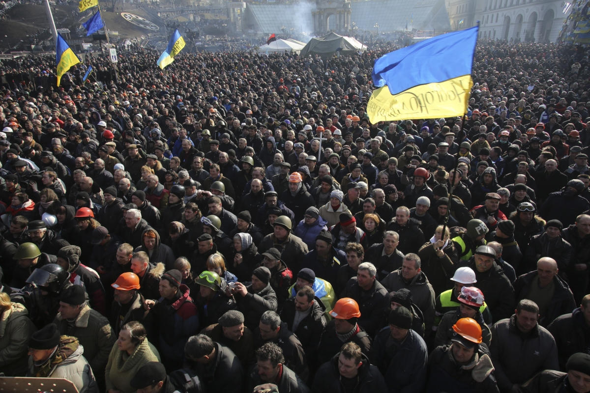 People listen to police officers from Lviv who have joined anti-government protesters as they speak from a stage during a rally in Independence Square