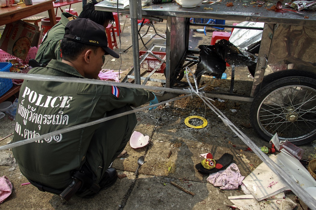 Thai police officers inspect the site of an explosion scene during an anti-government protest at Khao Saming district, Trat province February 23, 2014.