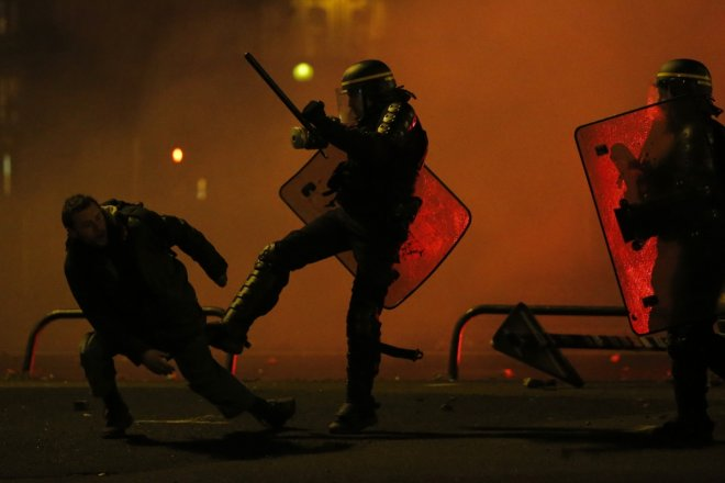 A protester is kicked by a French riot policeman during clashes