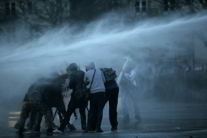 Masked protesters are sprayed by a water canon