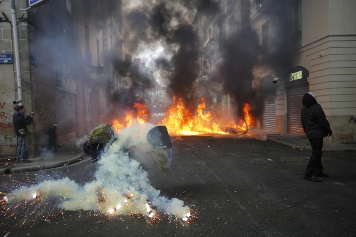 A tear gas grenade explodes near a masked protester