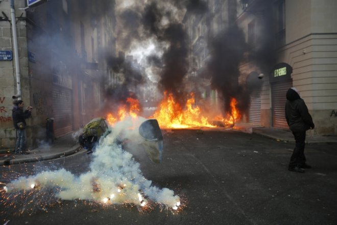 A tear gas grenade explodes near a masked protester