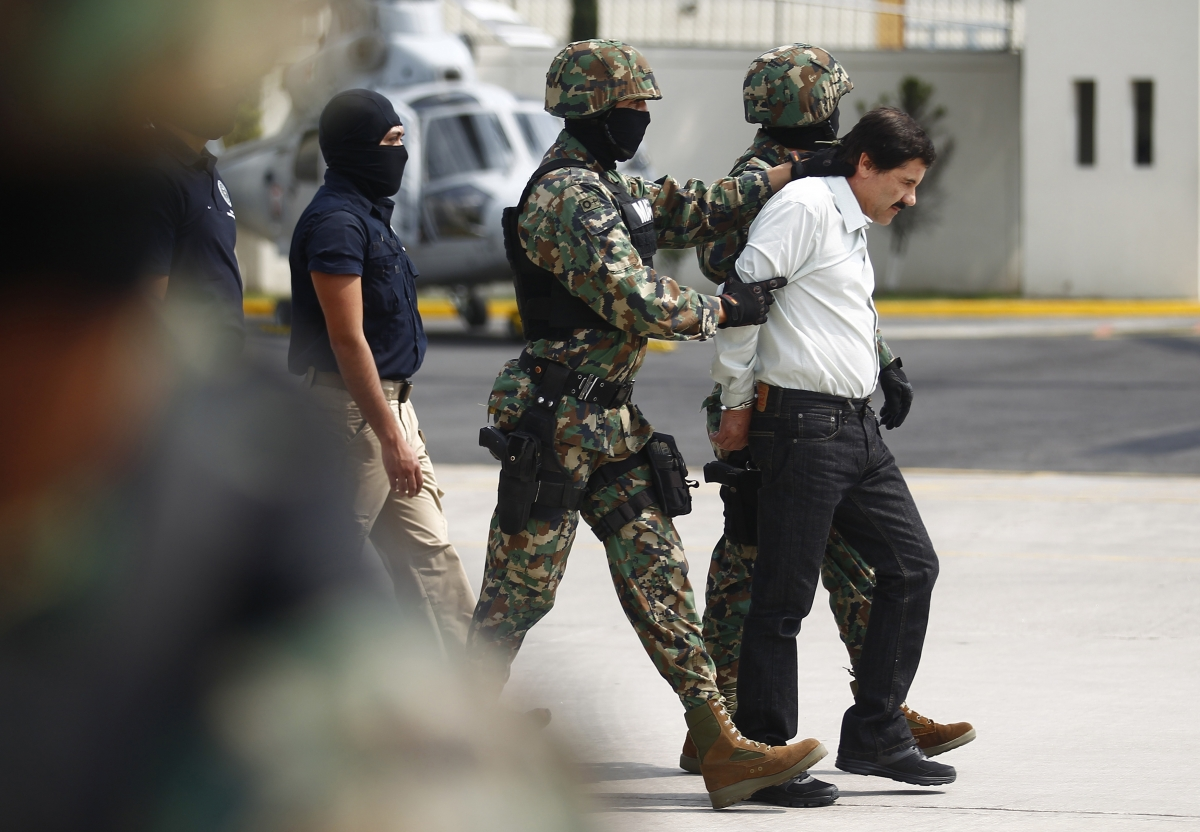 Guzman is escorted to a waiting heicopter by marines.