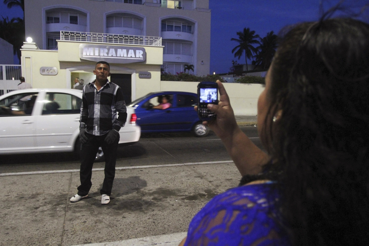 A man poses for a picture outside the apartment buildin in Mazatlan where Guzman was seized.