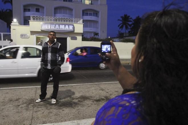 A man poses for a picture outside the apartment buildin in Mazatlan where Guzman was seized.