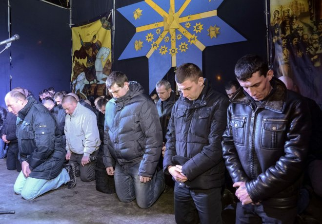 Local riot police kneel as they apologize to Lviv residents for taking part in an operation against anti-government protesters in Kiev