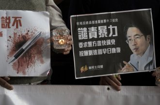 Pro-democracy activists hold a sign with an image of former chief editor of the Ming Pao daily Kevin Lau Chun-to as they attend a candlelight vigil to urge the police to solve the stabbing incident involving Lau