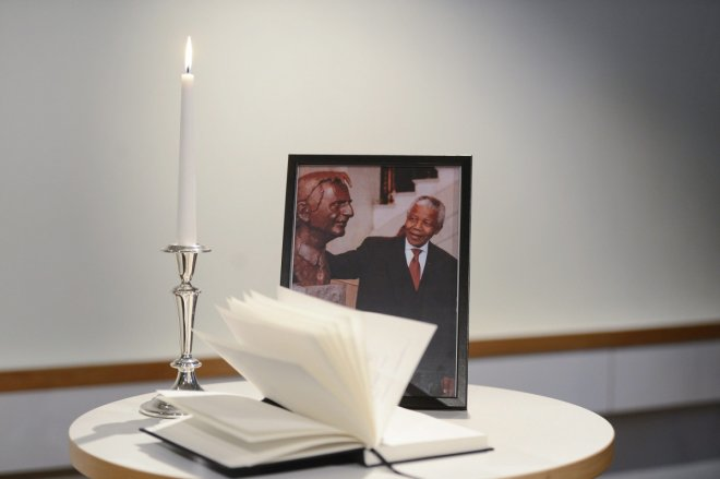 A condolence book is seen together with a photograph of late South African President Nelson Mandela posing beside the statue of former Social Democratic Party leader Olof Palme
