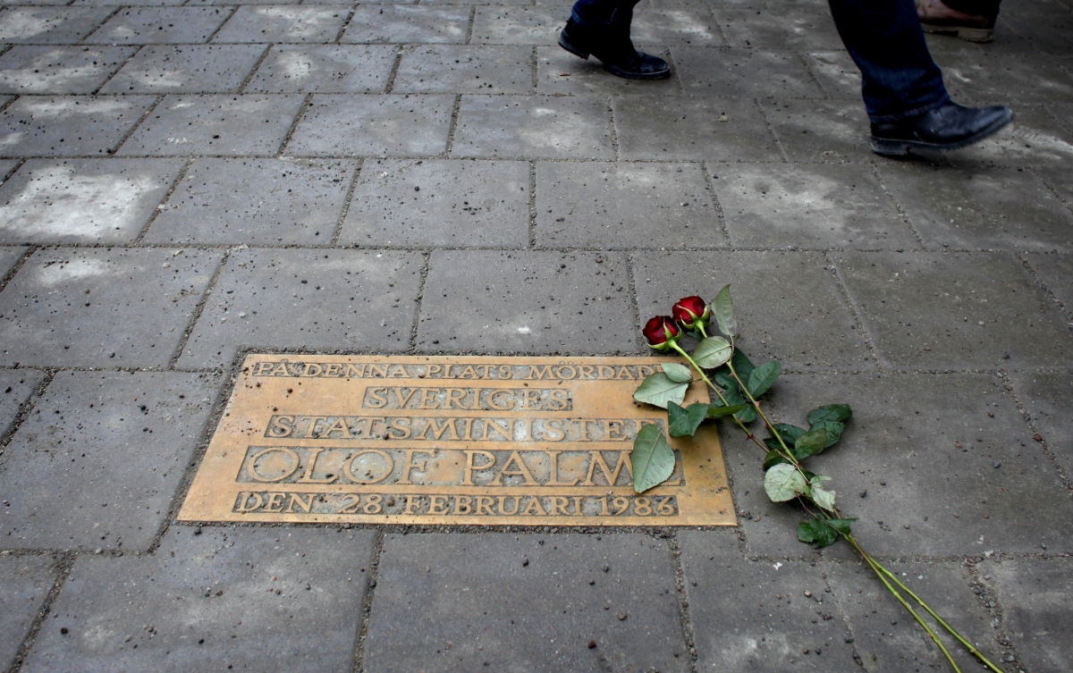 Pedestrians walk past a plaque marking the location where Swedish Prime Minister Olof Palme was shot and killed