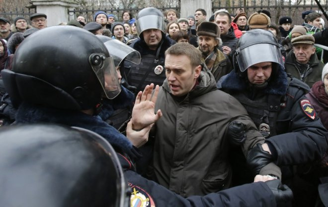 Police detain opposition leader Alexei Navalny outside a courthouse in Moscow