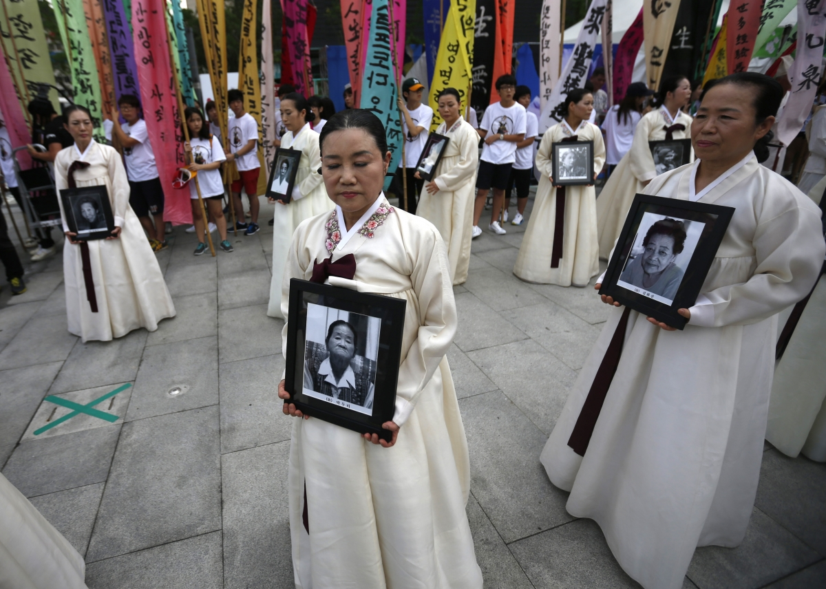 Participants carry the portraits of Korean women who were made sex slaves by the Japanese military during World War II