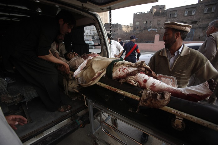 An injured man is carried out of an ambulance in Peshawar, northwest Pakistan.