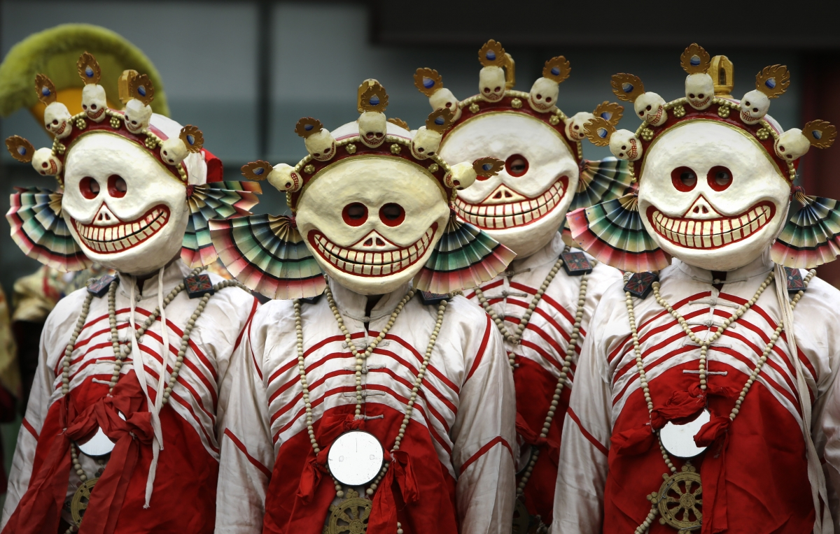 Monks dressed as Tibetan Buddhism characters attend a religious ceremony, known as