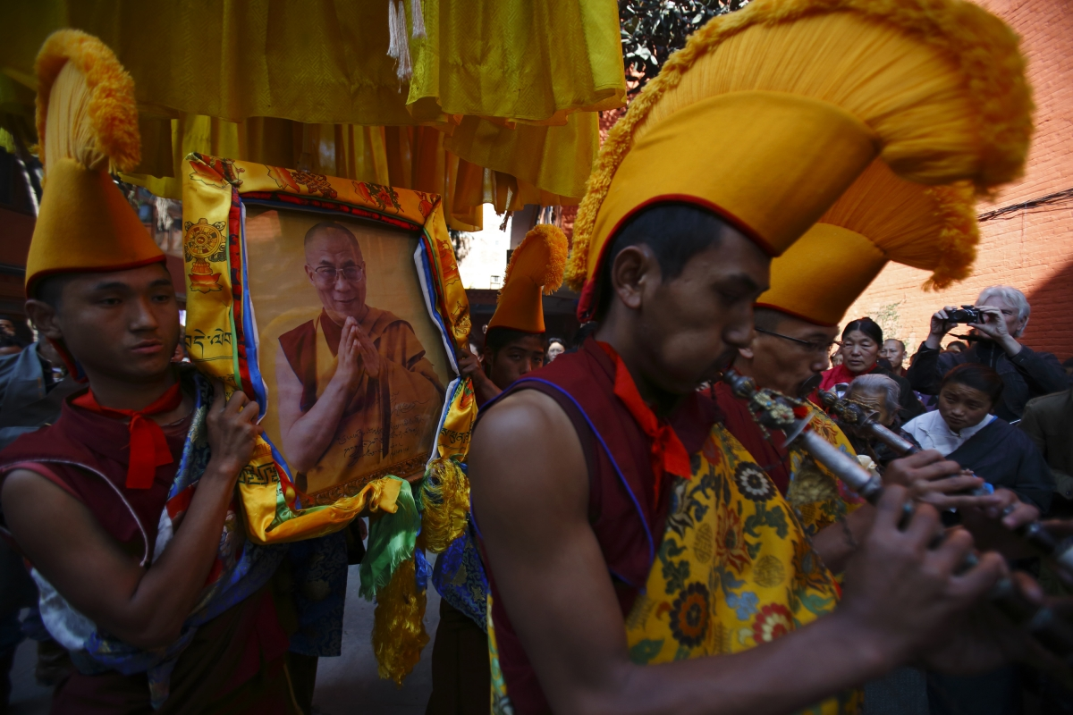 Tibetan monks carry a portrait of their spiritual leader Dalai Lama while performing rituals