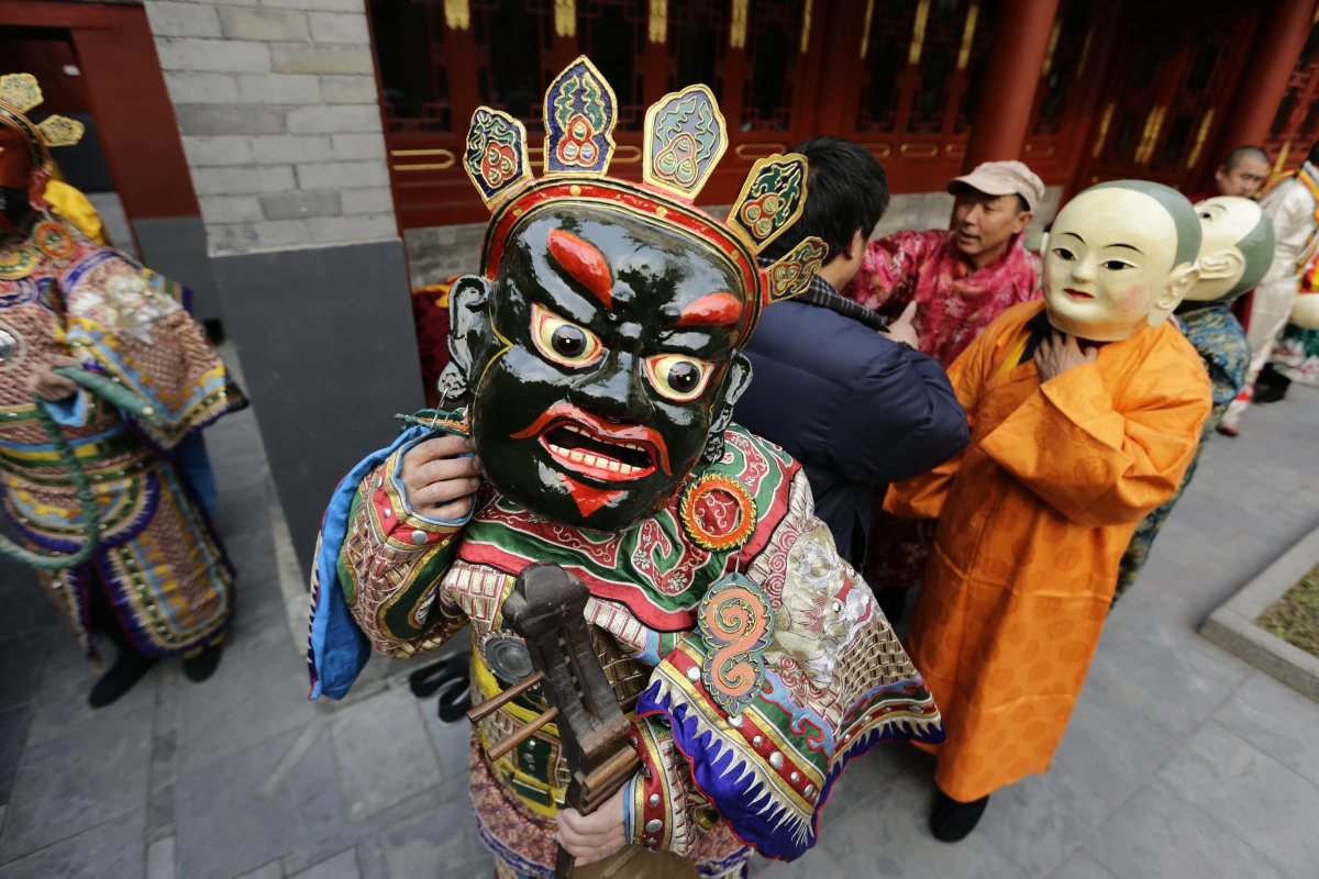 A Tibetan monk adjusts his mask while preparing for a religious ceremony, known as