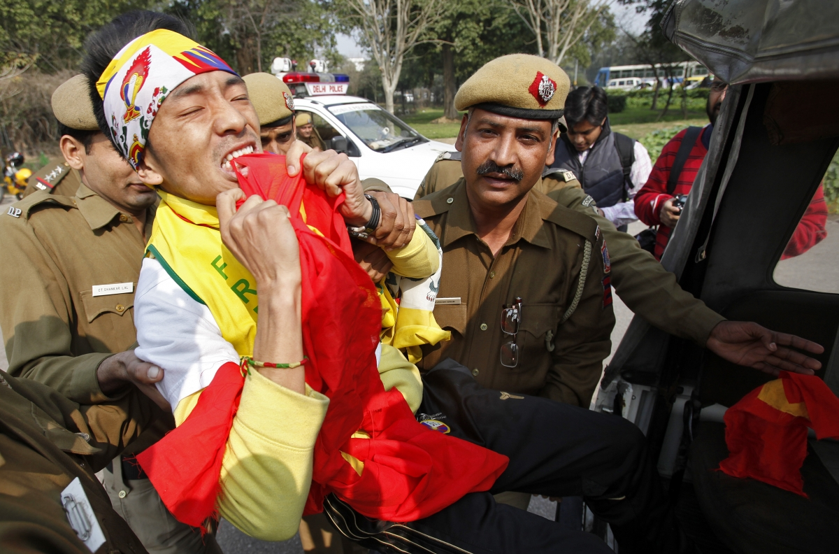 A Tibetan exile rips into a Chinese flag as he is detained by police during a protest in front of the Chinese embassy in New Delhi