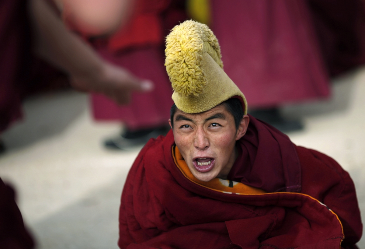 A monk's fury as he participates in a debate as part of Tibetan New Year celebrations at a temple in Langmusixiang, Sichuan Province