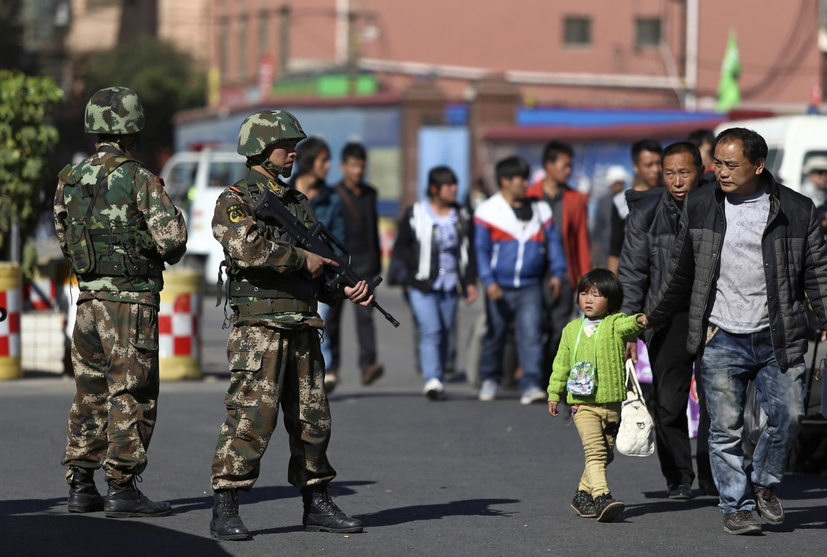 Paramilitary policemen patrol the streets after a knife attack at Kunming railway station, Yunnan province