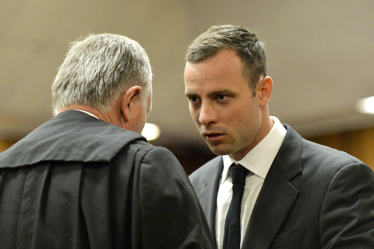 Oscar Pistorius consults with his lawyer Barry Roux on day one of his trial for killing Reeva Steenkamp
