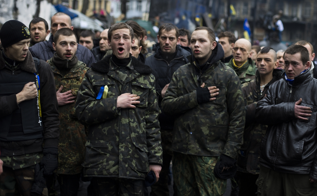 "Members of a ""Maidan"" self-defense battalion sing the Ukrainian national anthem before remembering fallen comrades at the site of recent street battles near Independence Square in Kiev"