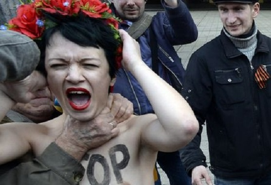 A bare breasted Femen activist is throttled during clashes between the radical feminists and paramilitary forces in Simferpol