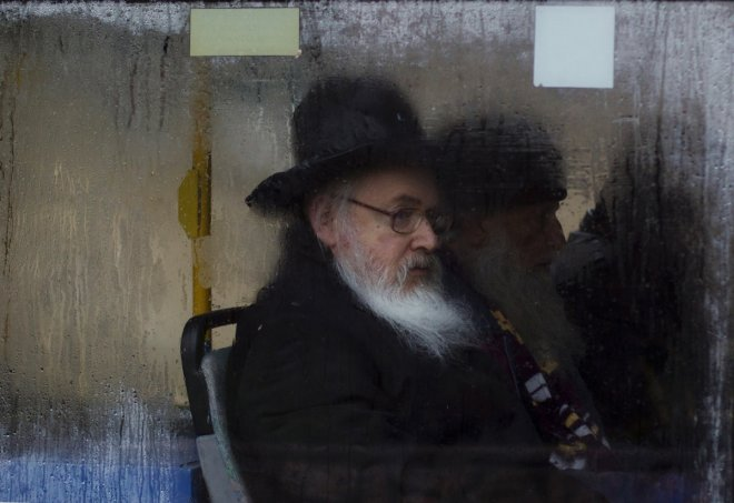 An Ultra-Orthodox Jewish man looks out of a fogged up bus window in Jerusalem