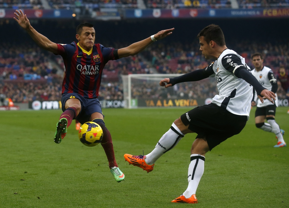 Barcelona's Alexis Sanchez (L) fights for the ball against Valencia's Juan Bernat during their Spanish first division soccer match at Camp Nou stadium in Barcelona February 1, 2014.