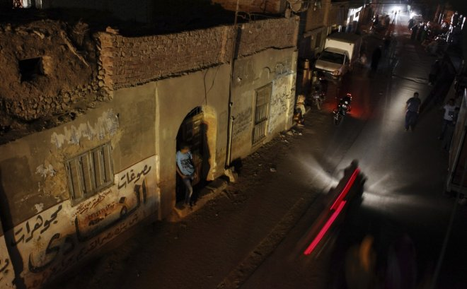People and vehicles are seen during a power cut in Toukh, El-Kalubia governorate, about 25 km (16 miles) northeast of Cairo May 26, 2013.