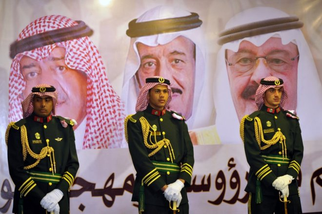 Saudi royal guards stand on duty in front of portraits of King Abdullah bin Abdulaziz (R), Crown Prince Salman bin Abdulaziz (C) and second deputy Prime Minister Muqrin bin Abdulaziz during the traditional Saudi dance known as