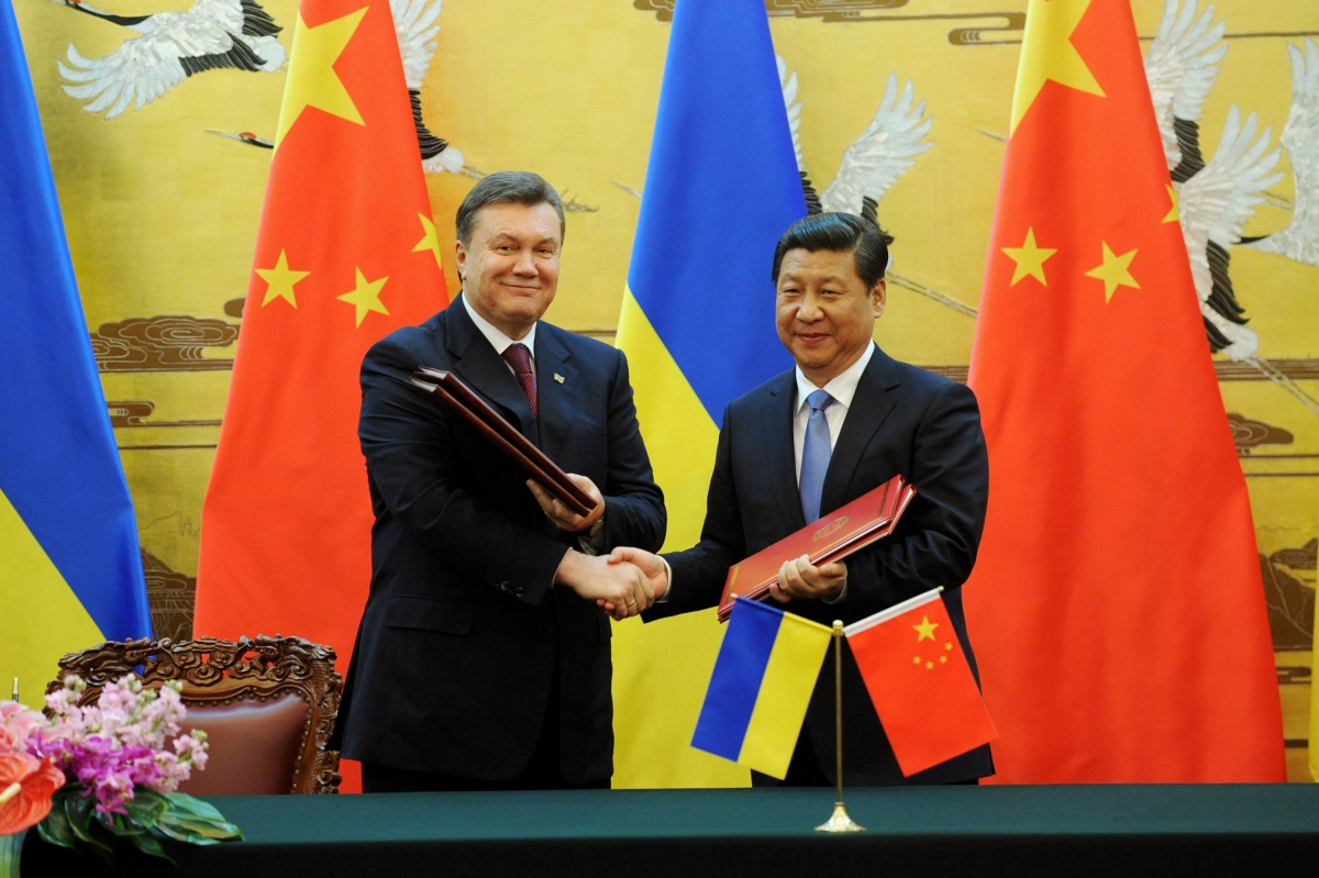 Ukraine's ousted President Viktor Yanukovich (L) shakes hands with Chinese President Xi Jinping