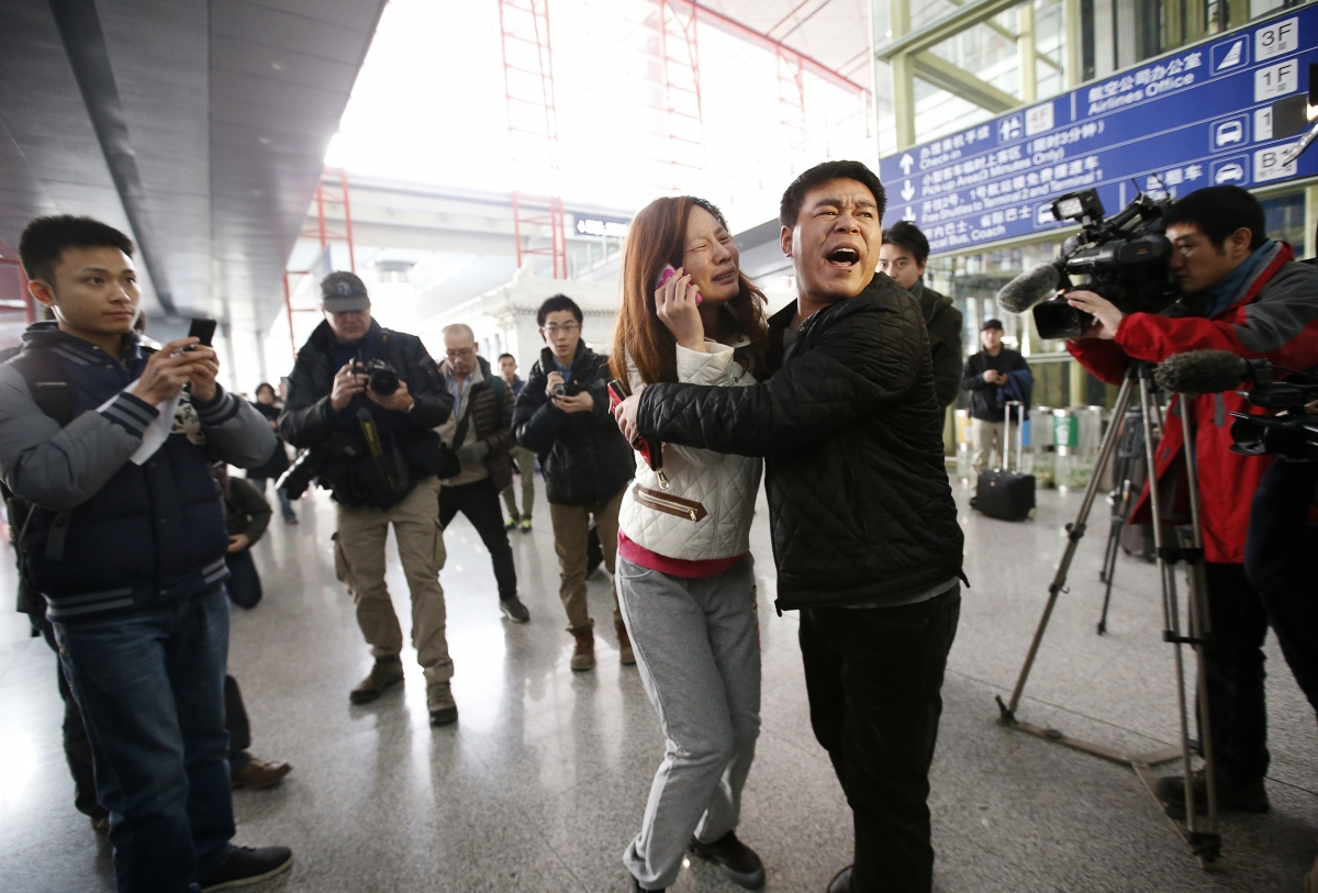 A relative (woman in white) of a passenger onboard Malaysia Airlines flight MH370 cries as she talks on her mobile phone at the Beijing Capital International Airport in Beijing March 8, 2014.