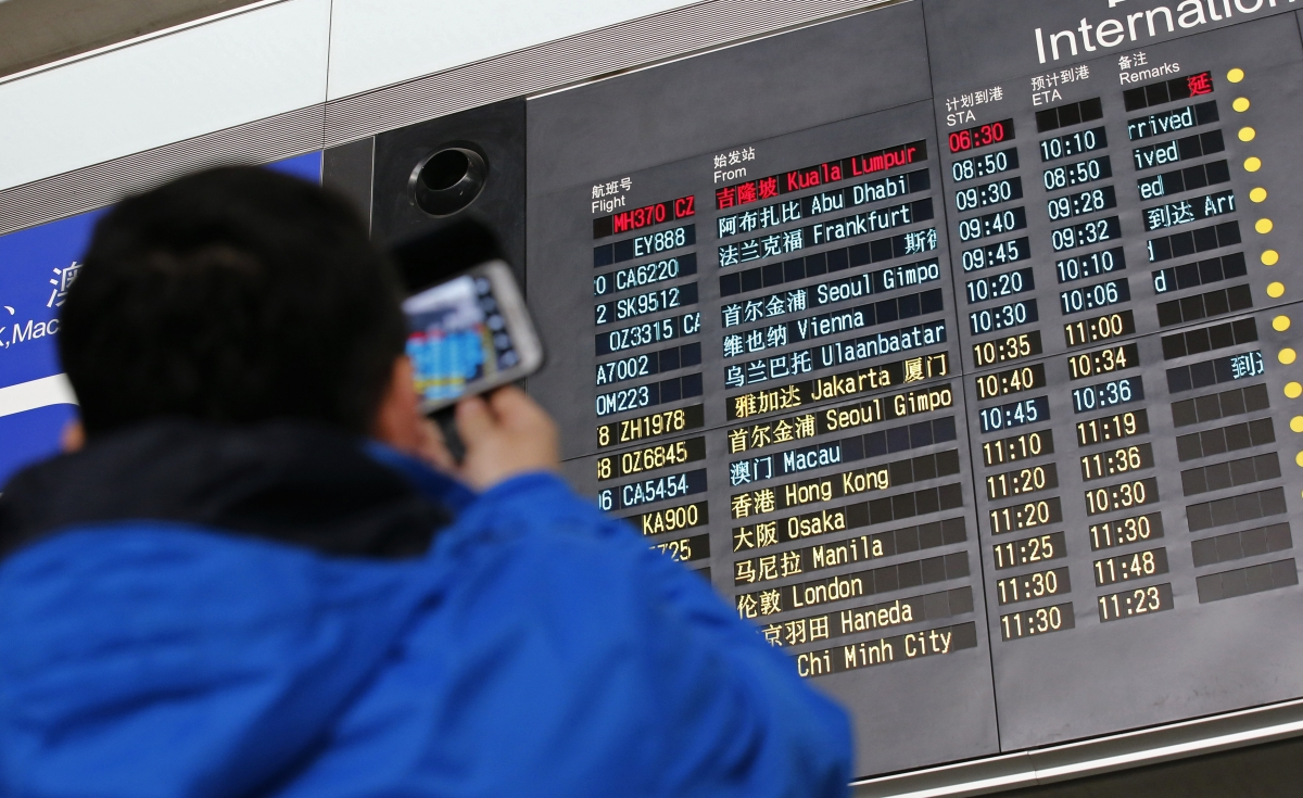 A man takes pictures of a flight information board displaying the Scheduled Time of Arrival (STA) of Malaysia Airlines flight MH370 (top, in red) at the Beijing Capital International Airport in Beijing, March 8, 2014.