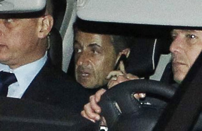 Former French president Nicolas Sarkozy speaks on the phone after leaving a courthouse in Bordeaux in November, 2012.