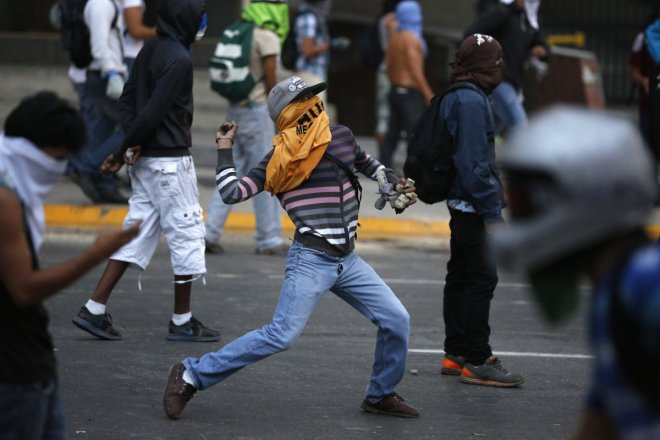 Anti-government protesters throw stones during a protest against Nicolas Maduro's government in Caracas March 7