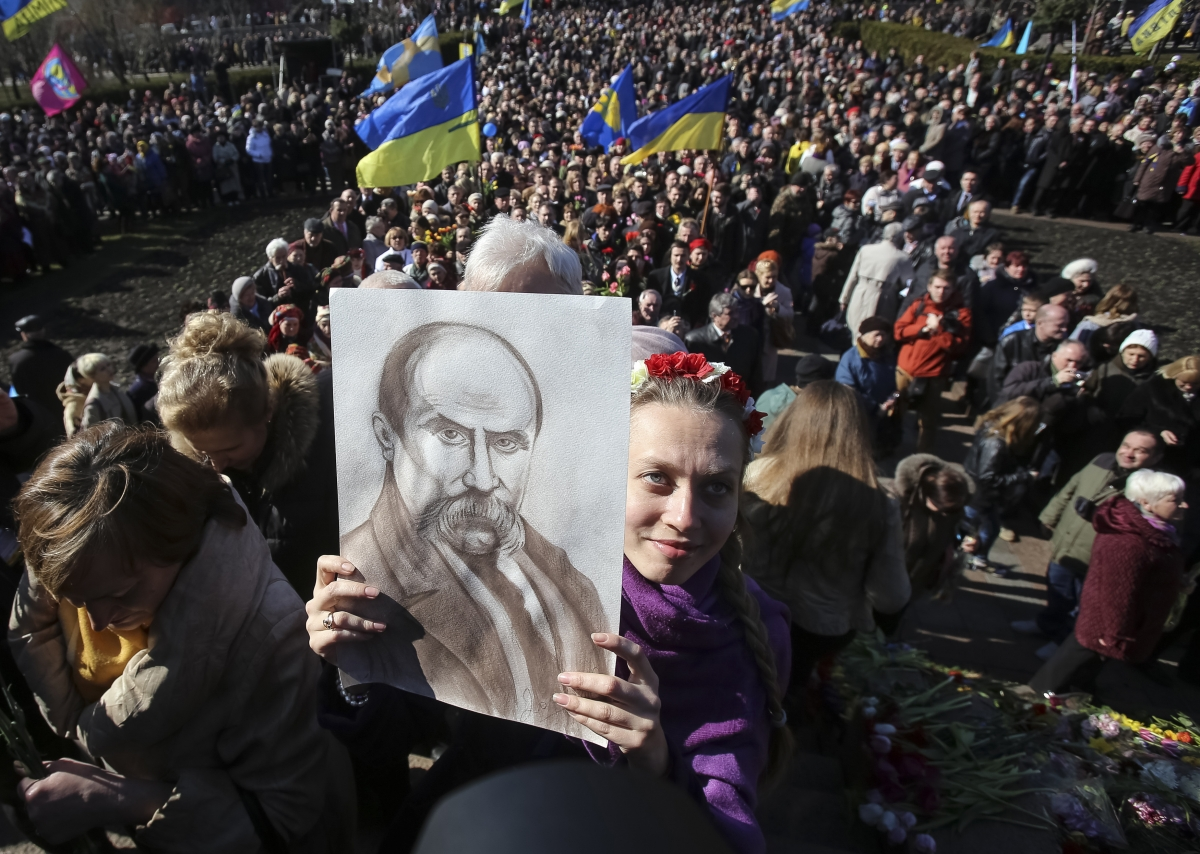 A woman holds a picture of Ukranian poet Taras Shevchenko at a rally in Kiev, Ukraine this afternoon.