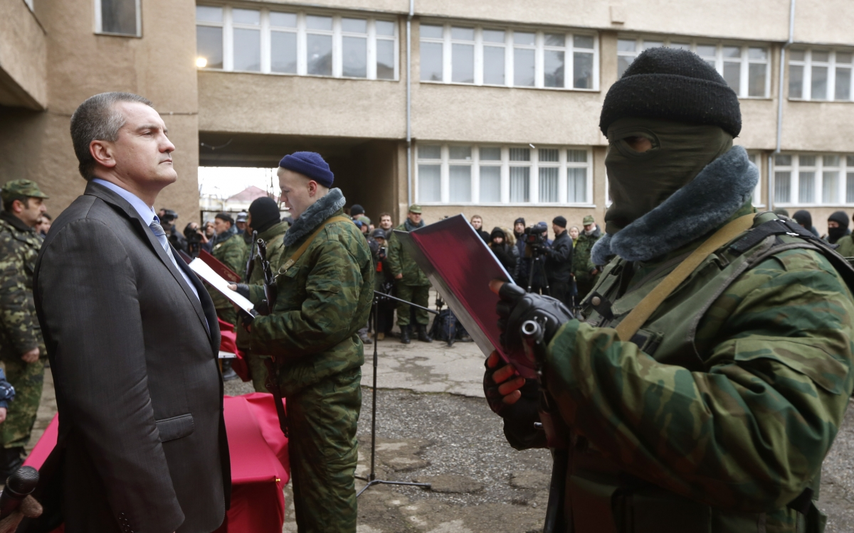 Sergei Aksyonov, Crimea's pro-Russian prime minister, stands as a member of a pro-Russian self defence unit takes an oath to Crimea government in Simferopol
