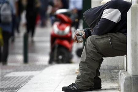 A beggar is seen on a street in central Athens