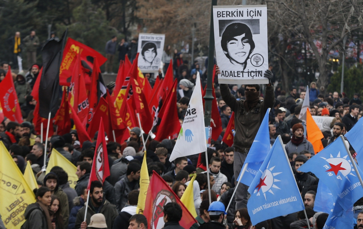A demonstrator holds up a poster of Berkin Elvan, which reads: