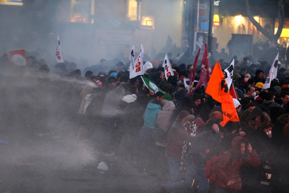 Anti-government protesters run as riot police fires a water cannon during a demonstration in Ankara