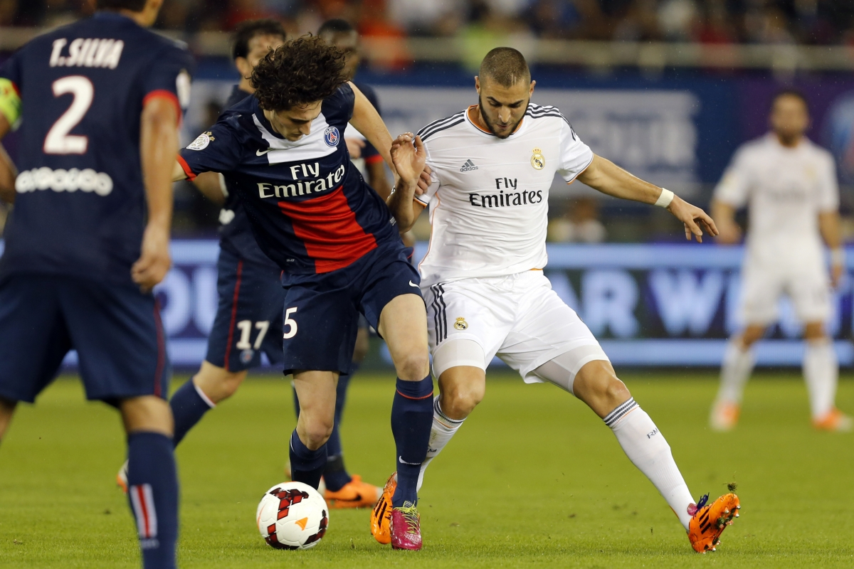 Adrien Rabiot challenges Real Madrid's Karim Benzema during their friendly match in Doha.