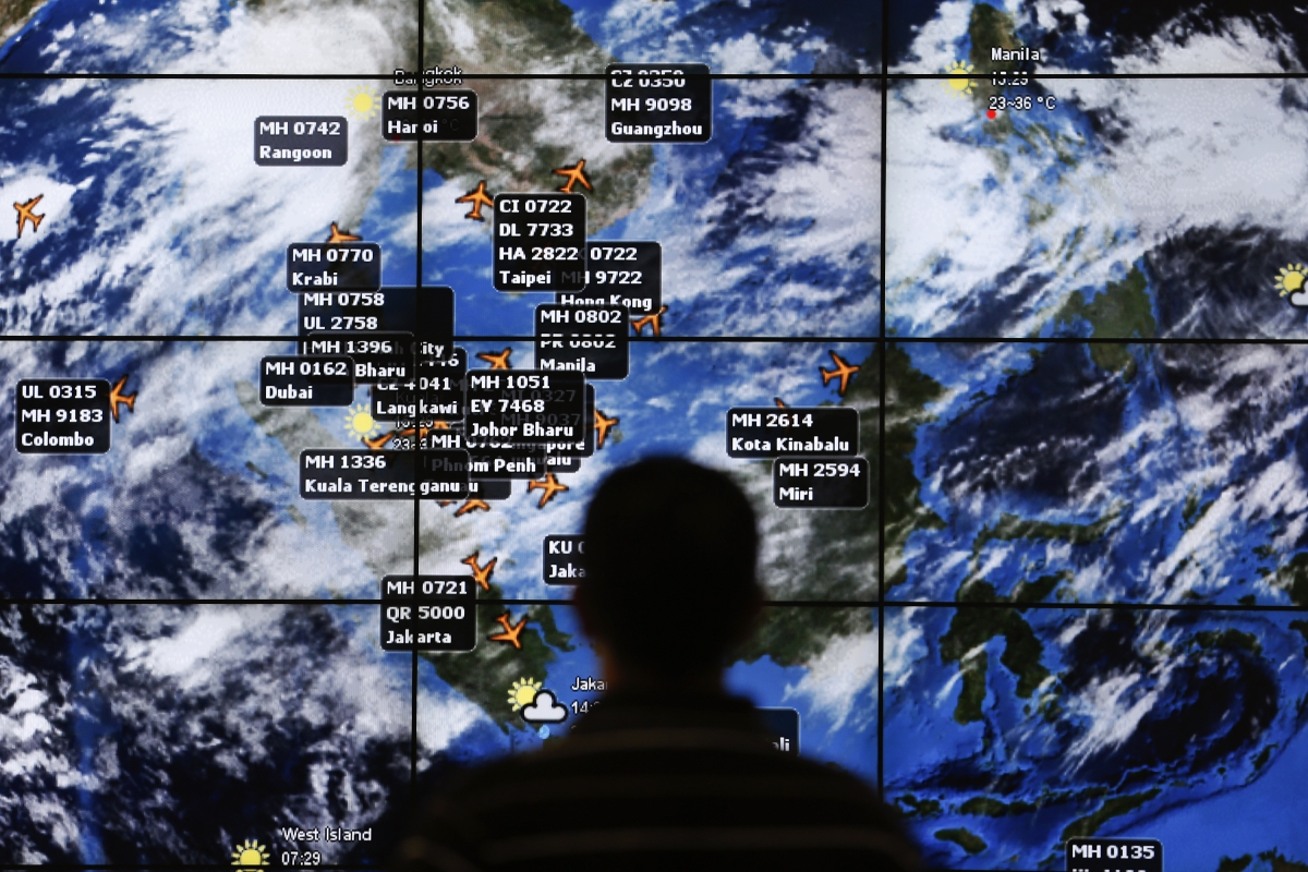 man watches a large screen showing different flights at the departure hall of Kuala Lumpur International Airport