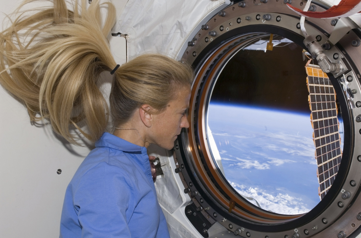 Astronaut Karen Nyberg looks through a window in the Kibo laboratory of the International Space Station