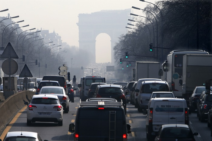 Rush hour traffic on a smoggy avenue leading up to the Arc de Triomphe in western Paris.