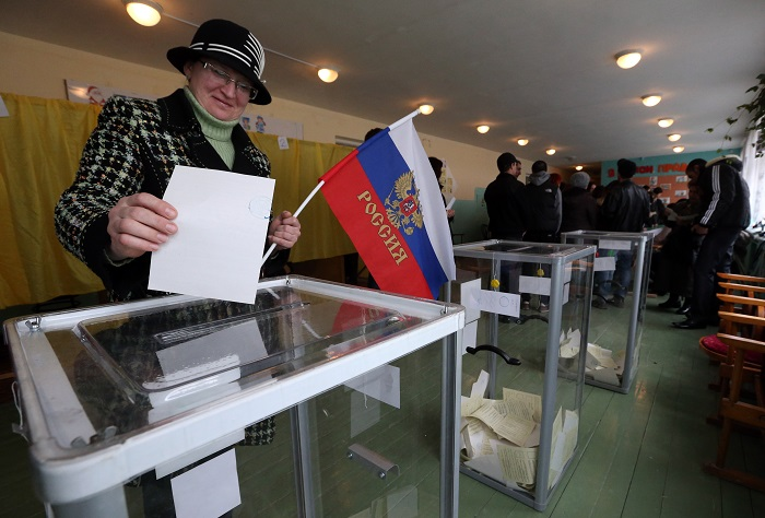 A woman casts her ballot in the Crimea referendum while holding a Russian flag.