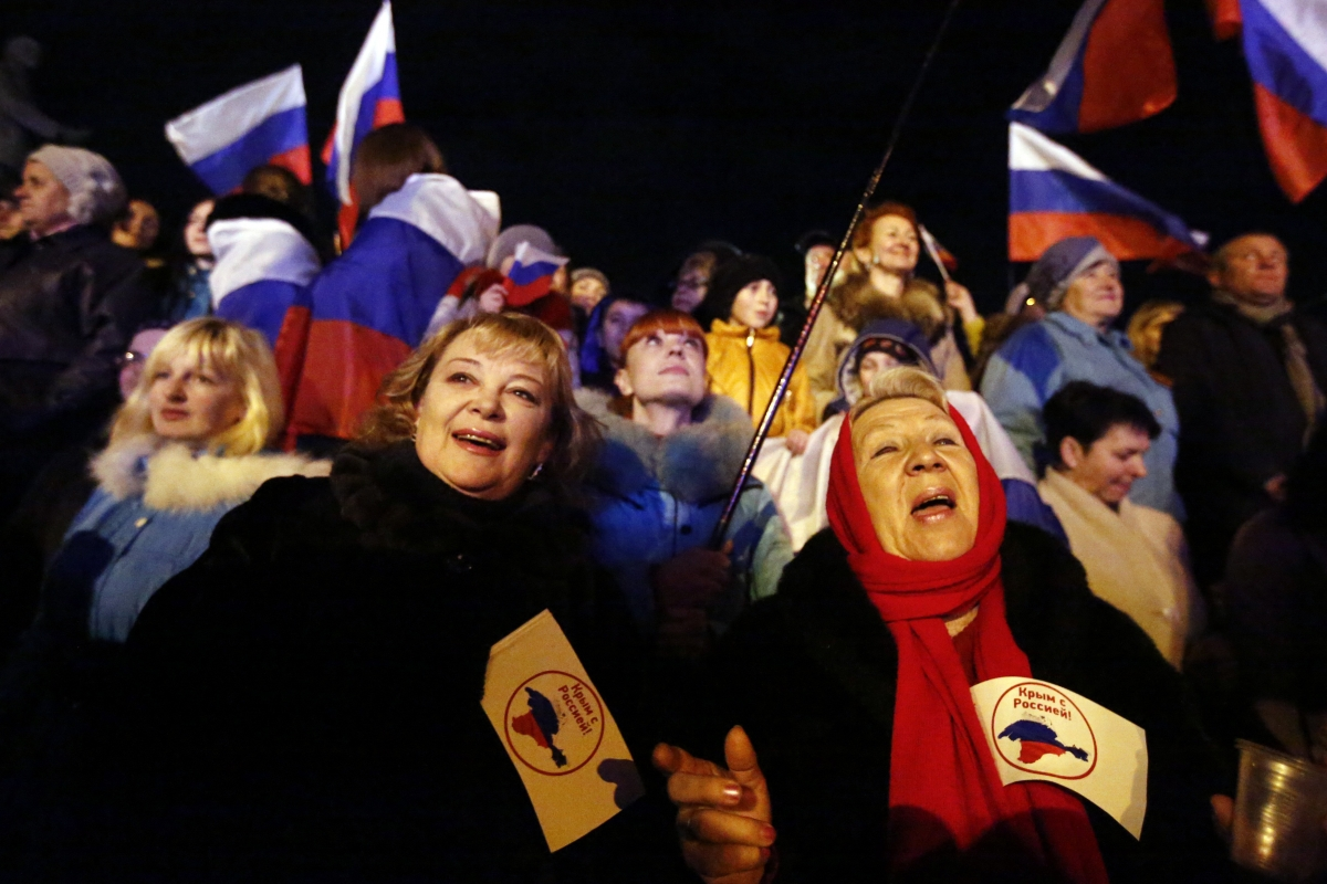 """Two women hold flags reading """"Crimea is with Russia"""" as people wait for the announcement of preliminary results of today's referendum on Lenin Square in the Crimean capital of Simferopol"""